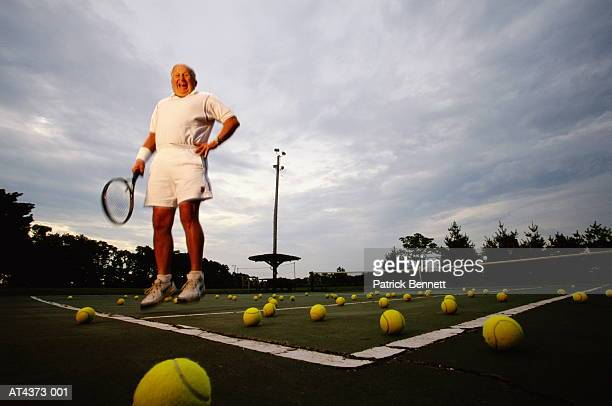 Mature man jumping on tennis court with many tennis balls, low angle