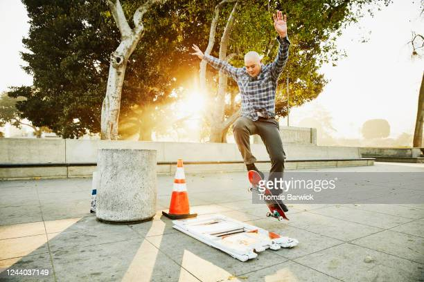 mature man jumping over barricade while skateboarding in park - individuality stock pictures, royalty-free photos & images