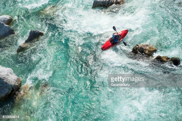 mature man kayaking on  river soca rapids - high angle view - coraggio foto e immagini stock