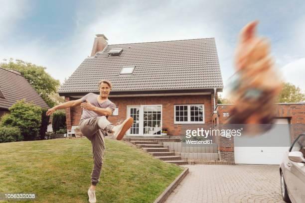 mature man kicking away garden gnome in front of his home - aufstand stock-fotos und bilder