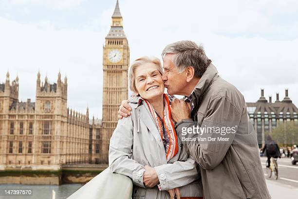 mature man kisses woman in front of big ben. - clock tower stock pictures, royalty-free photos & images