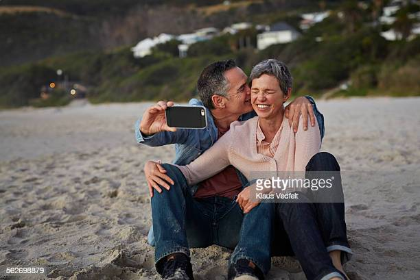 mature man kissing girlfriend while making selfie - 50 59 years stock pictures, royalty-free photos & images