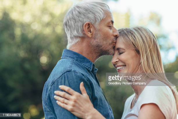 mature man kissing his wife on her forehead outside - forehead stock pictures, royalty-free photos & images