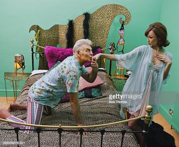 Mature man kissing woman's hand in bedroom