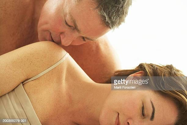 Mature man kissing woman's shoulder, close-up