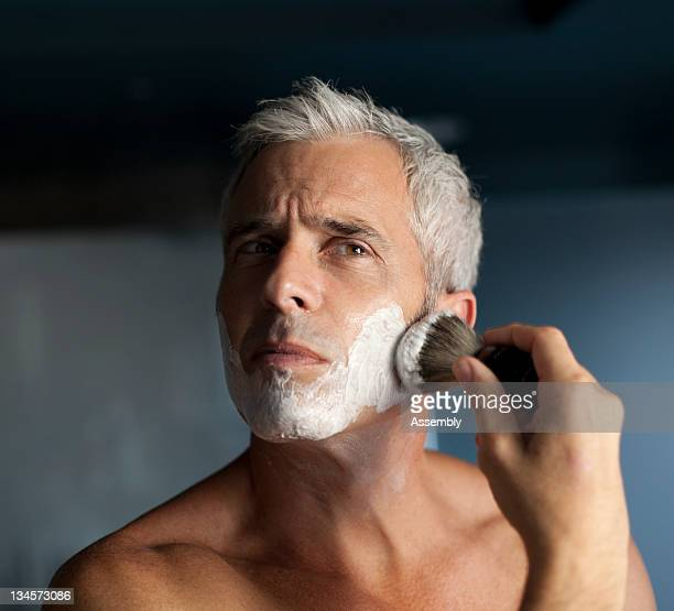Mature man lathering face before shaving