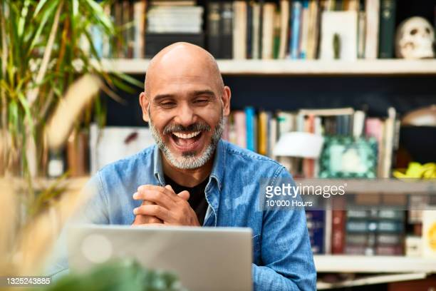 mature man laughing and smiling on video conference - one mature man only stock pictures, royalty-free photos & images