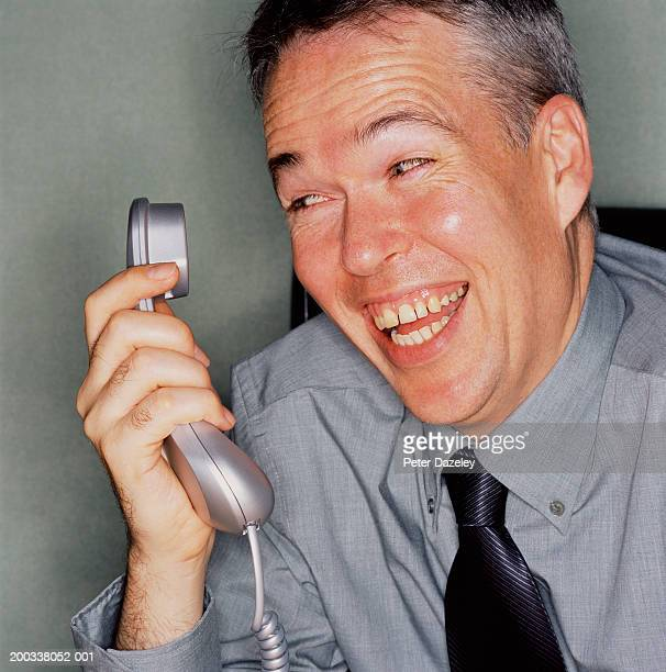 Mature man laughing at  telephone receiver in hand, close-up