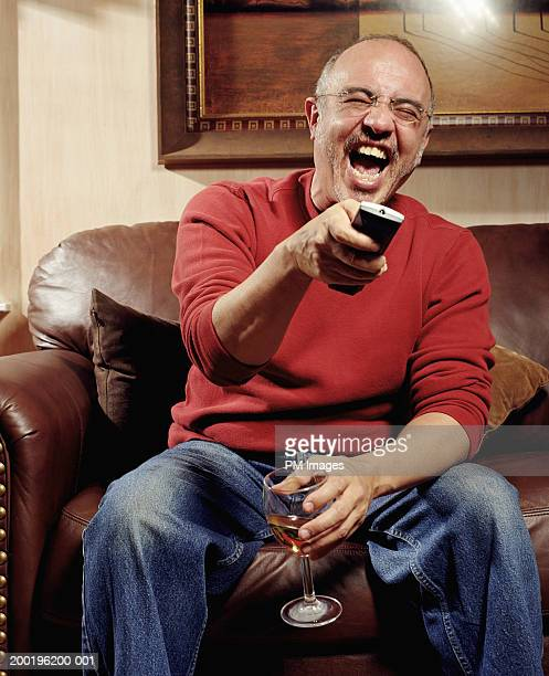 mature man laughing, pointing television remote control - aiming stock pictures, royalty-free photos & images
