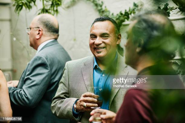 Mature man laughing with friend during cocktail party