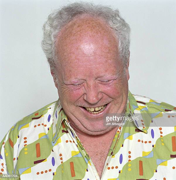 Mature man laughing with head down, close-up