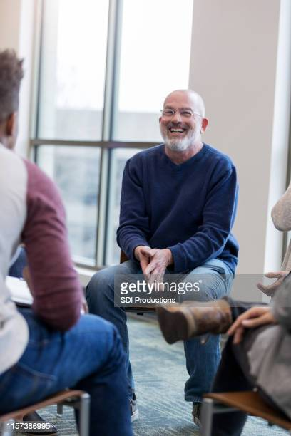 mature man laughs when unrecognizable teen makes a joke - group therapy stock pictures, royalty-free photos & images