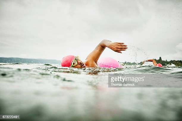 mature man leading early morning open water swim - effort stock pictures, royalty-free photos & images
