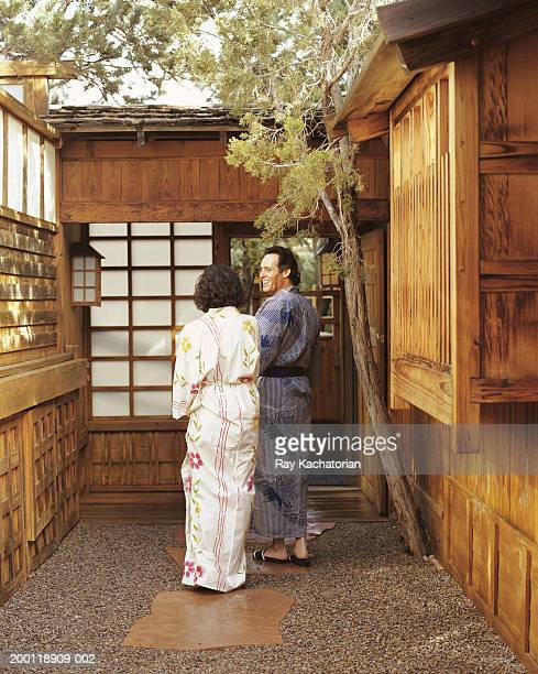 Mature man leading woman into Japanese structure
