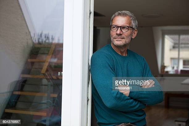 mature man leaning against balcony door - long sleeved stock photos and pictures