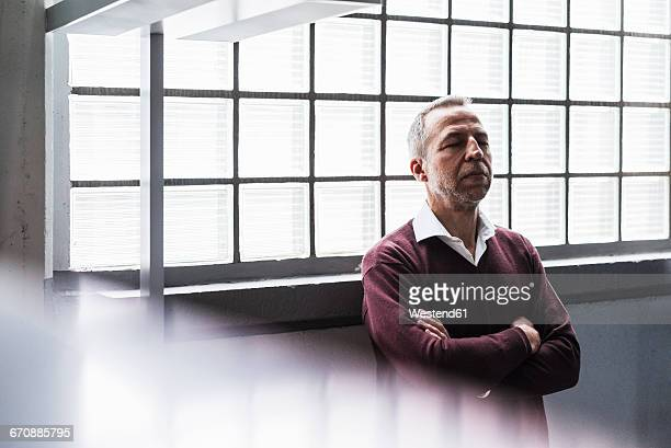 Mature man leaning against glass brick wall with eyes closed