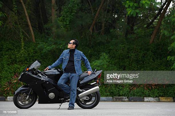 Mature man leaning against motorcycle, wearing sunglasses