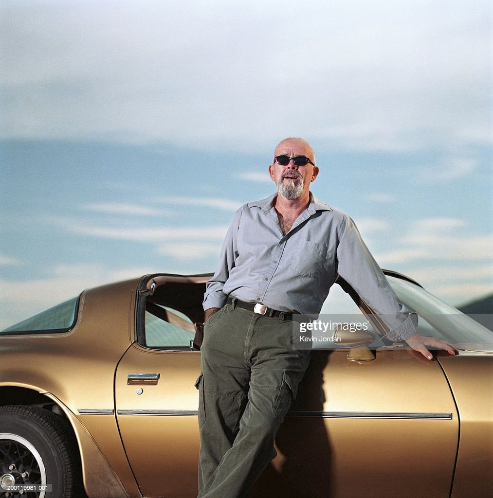 Mature man leaning against sports car, portrait : Stock Photo
