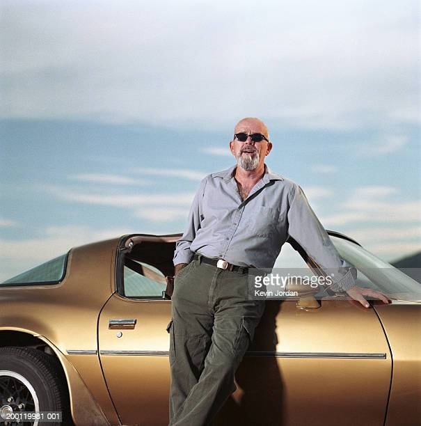 mature man leaning against sports car, portrait - bling bling stock pictures, royalty-free photos & images