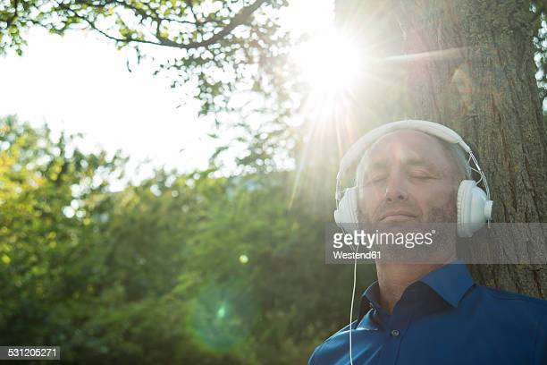 Mature man leaning against tree trunk listening to music
