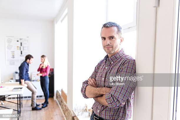 Mature man leaning against window arms crossed looking at camera smiling