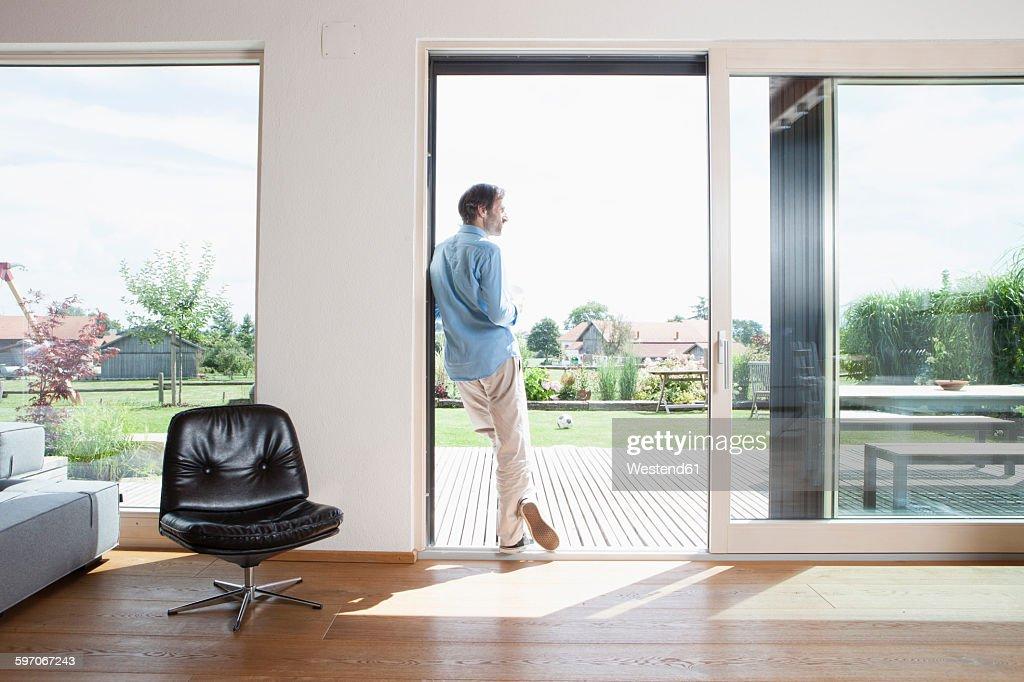 Mature man leaning in garden door, rear view : Stock Photo