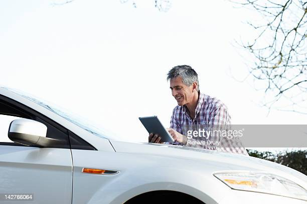 mature man leaning on car using digital tablet - richard drury stock pictures, royalty-free photos & images