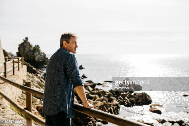 mature man leaning on railing while looking at sea during sunny day - vedação de corrimão imagens e fotografias de stock