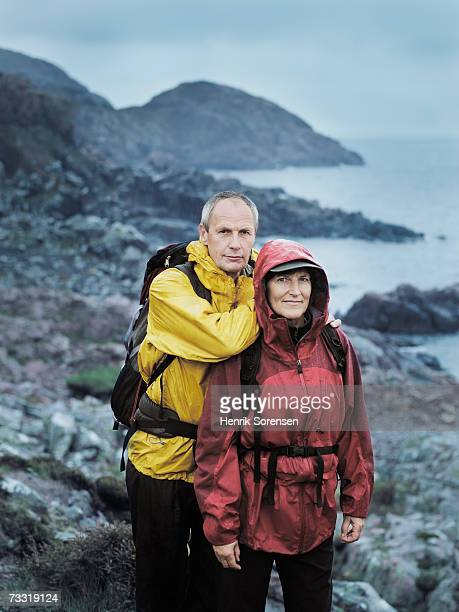 Mature man leaning on woman on nature trail in rain