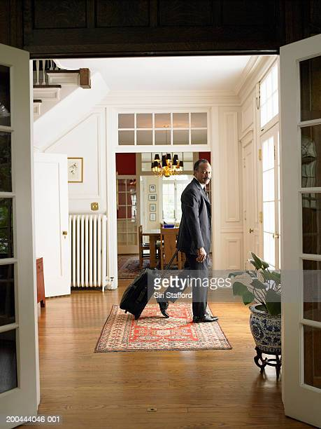 Mature man leaving home with luggage