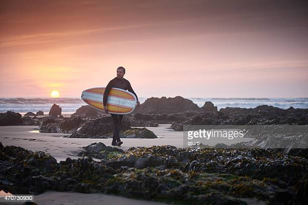 mature man leaving the surf at sunset
