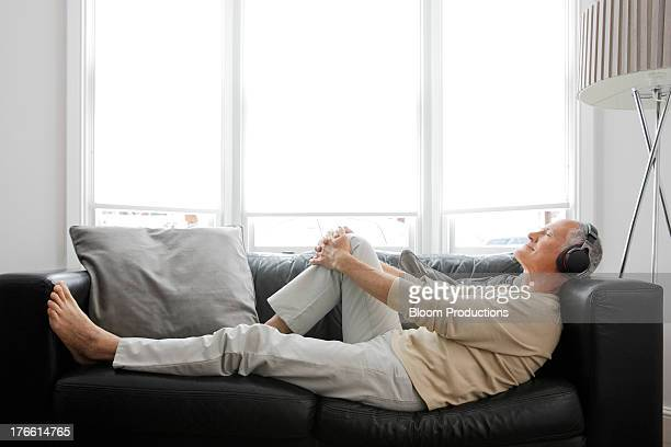 mature man listening to headphones - lying down stock pictures, royalty-free photos & images