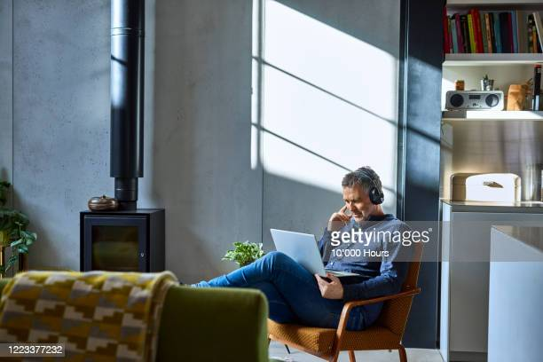 mature man listening to music on laptop - home interior stock pictures, royalty-free photos & images