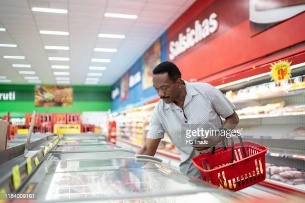homem maduro que olha e que escolhe o produto no congelador do supermercado - comida congelada - fotografias e filmes do acervo