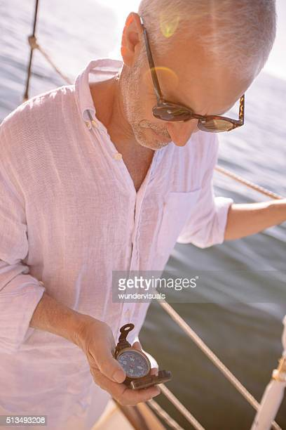 Mature man looking at a compass on a yacht