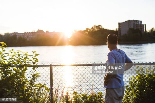 a mature man looking at a river at sunset - solar flare stock pictures, royalty-free photos & images