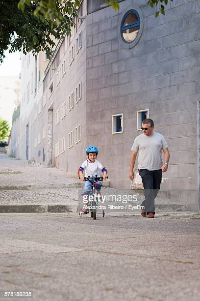 Mature Man Looking At Boy Riding Bicycle In City