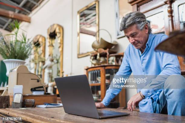 Mature man looking at computer in his antique shop