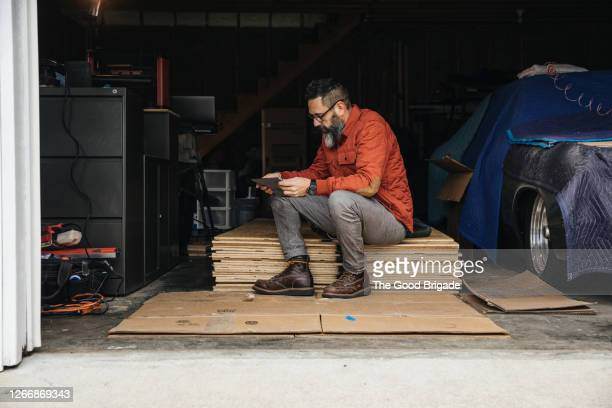 Mature man looking at digital tablet while sitting in garage