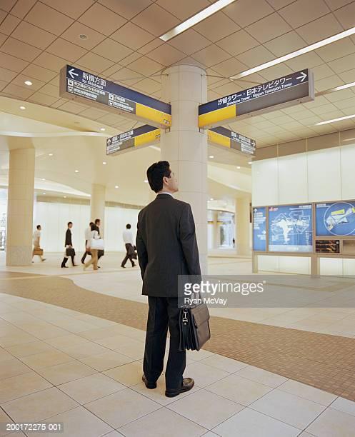成熟した男性の標識に従って、地下鉄駅、背面