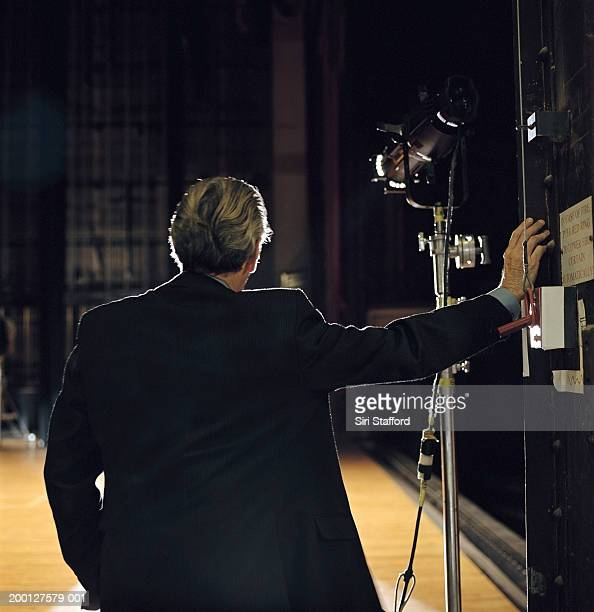Mature man looking at empty stage, rear view