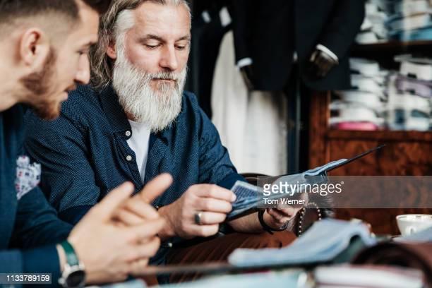 mature man looking at fabric swatches - herrenkleidung stock-fotos und bilder