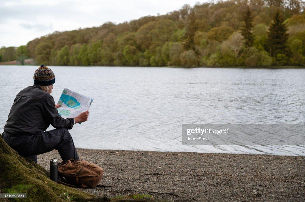 Mature man looking at his map : Stock Photo