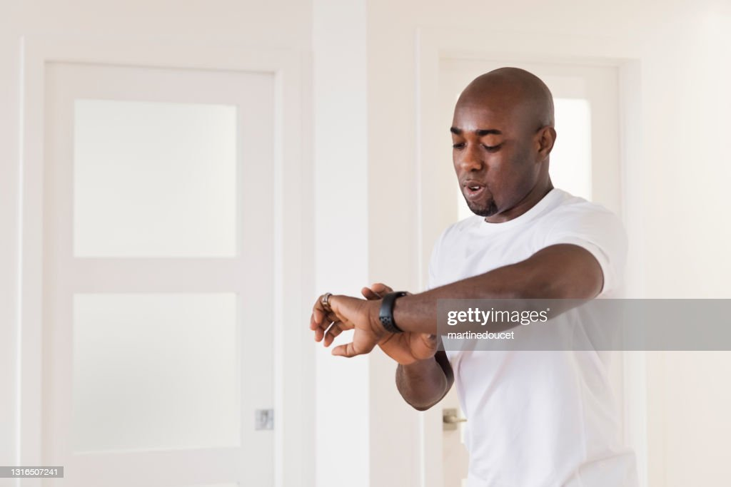 Mature man looking at his training watch at home. : Stock Photo