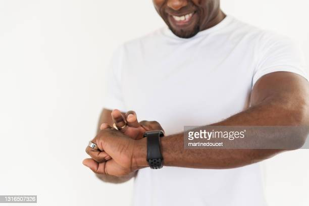 "mature man looking at his training watch at home. - ""martine doucet"" or martinedoucet stock pictures, royalty-free photos & images"