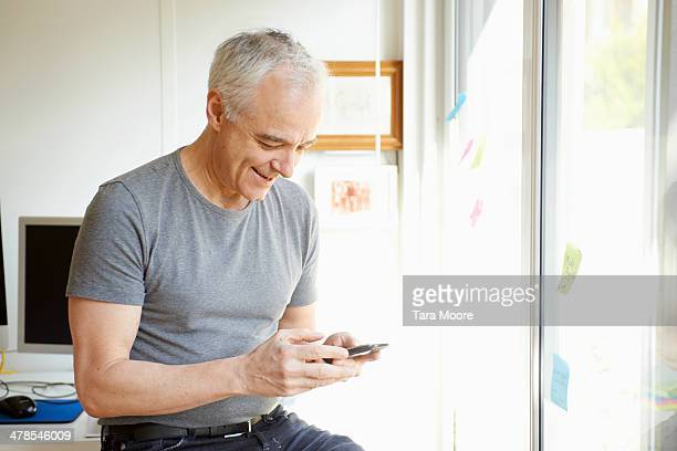 mature man looking at mobile in home office