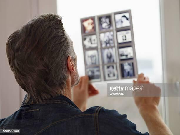 Mature man looking at old slides