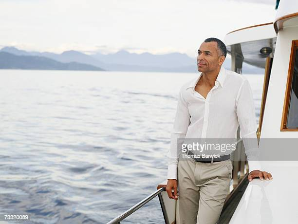 mature man looking at view from deck of yacht - ricchezza foto e immagini stock