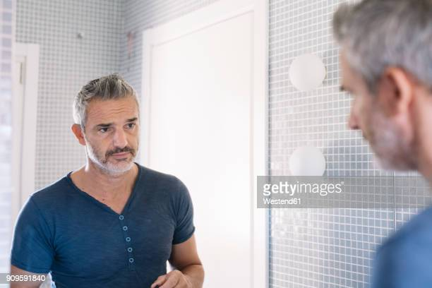 mature man looking in bathroom mirror - spiegel stockfoto's en -beelden