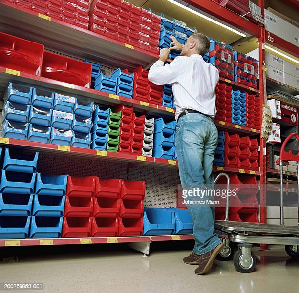 Mature man looking in container on shelf in hardware shop, rear view